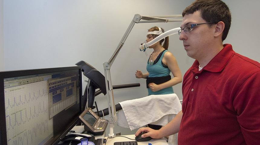 An EBL worker examines data while a woman runs on a treadmill wearing an oxygen mask
