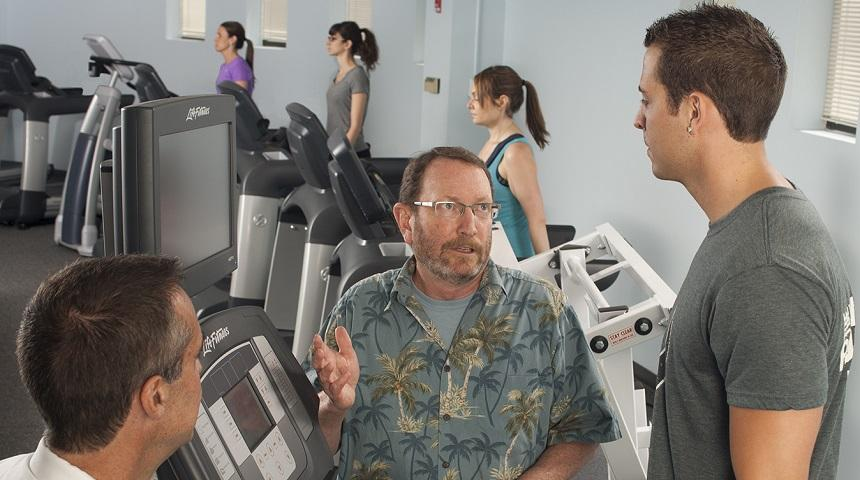 Several people are on treadmills. In the foreground, a participant on a treadmill is talking with an EBL worker.