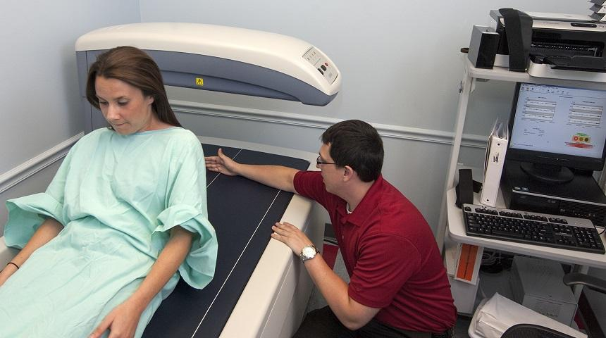 A patient lying on a table for testing with an EBL worker helping to administer a DEXA scan.